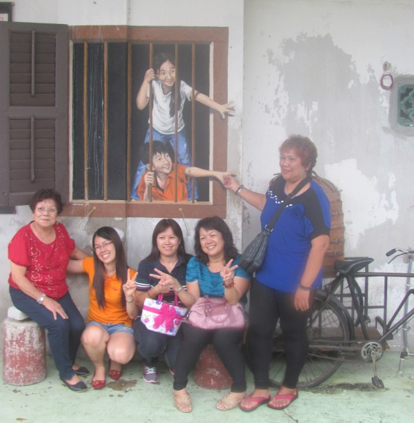eine chinesische Familie posiert vor einer Strassenmalerei in Georgetown, Penang, a Chinese family posing in front of a streetart painting in Georgetown, Penang