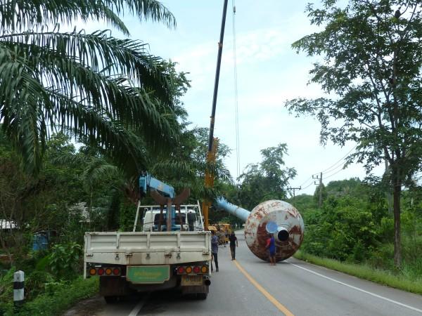 Straßenarbeiten: ein Wasserturm wird verladen, workers put a water tower on a truck