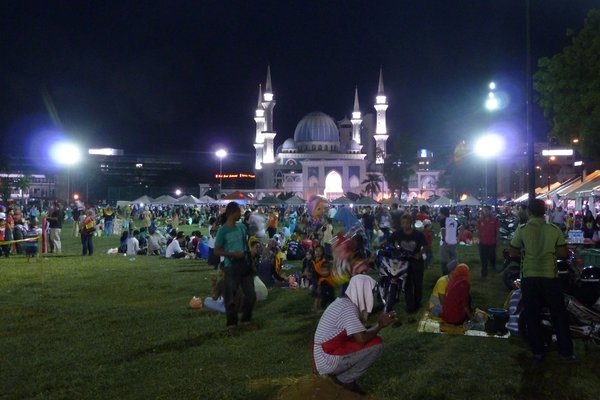 Kuantan bei Nacht während der Ramadanzeit - nach Sonnenuntergang darf wieder gegessen werden, die Menschen kaufen beim benachbarten Ramadanmarkt und picknicken vor der großen Moschee