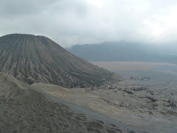 """Bromo - the view from the crater rim, down to the """"sea of sand"""", another vulcanic mountain and a Hindu temple. ///// Bromo - die Sicht hinunter vom Krater des Bromo auf das Sandmeer, einen anderen vulkanischen Berg und einen Hindu-Tempel."""