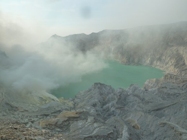 Ijen - the shiny colour of the crater lake is caused by the sulfur.  You can see the sulfur clouds rising in the left of the picture ///// Ijen - Die türkise Farbe des Vulkansees kommt durch den Schwefel zustande. Links im Bild sieht man den Schwefeldampf aufsteigen.