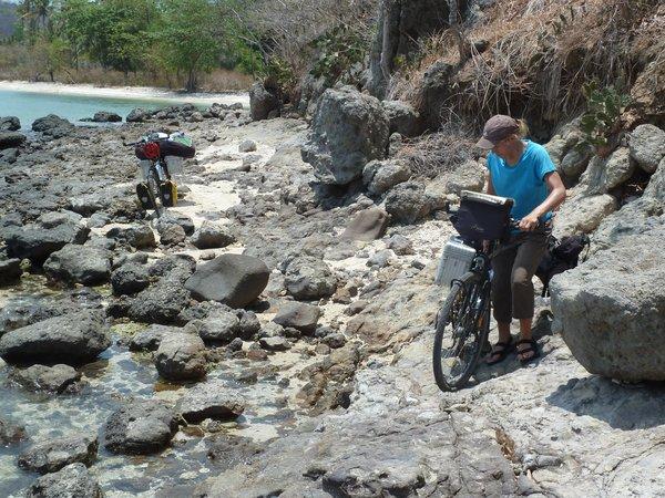 While cycling along the beach we have to push our bikes across some stones for about 100m, worth it though ///// Um am Strand entlangzuradeln müssen wir unsere Räder für ca. 100 m über Steine schieben, es lohnt sich aber