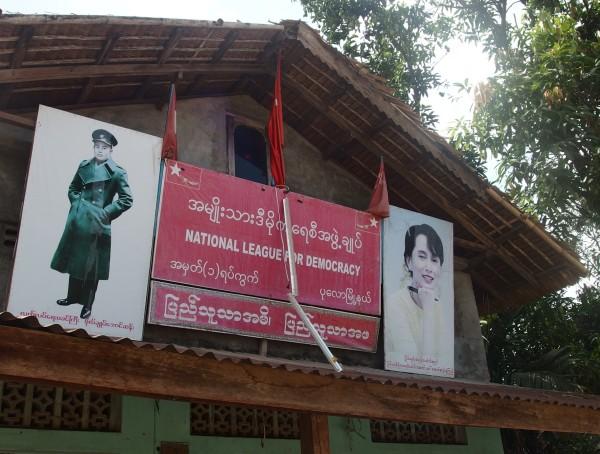 Wir sehen viele Parteibüros der NLD (National League for Democracy) mit Bildern der Friedensnobelpreisträgerin Aung San Suu Kyi und ihres Vaters Aung San, der eine entscheidende Rolle bei der Unabhängigkeit spielte; we see many offices of the NLD (National League for Democracy) with nobel peace prize winner Aung San Suu Kyi and her father Aung San